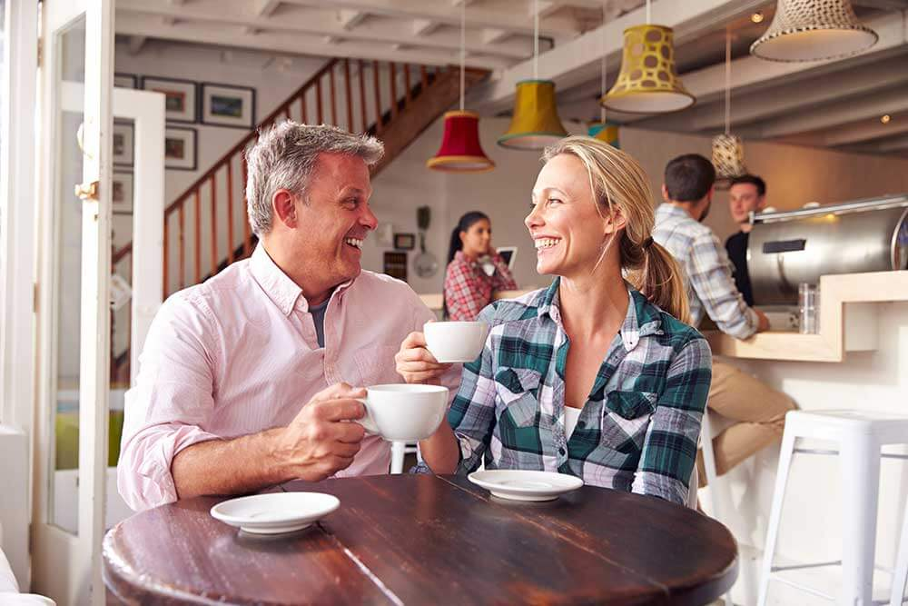 A man and a woman smile on a coffee date. Their teeth are white and they're showing the benefits of smiling.