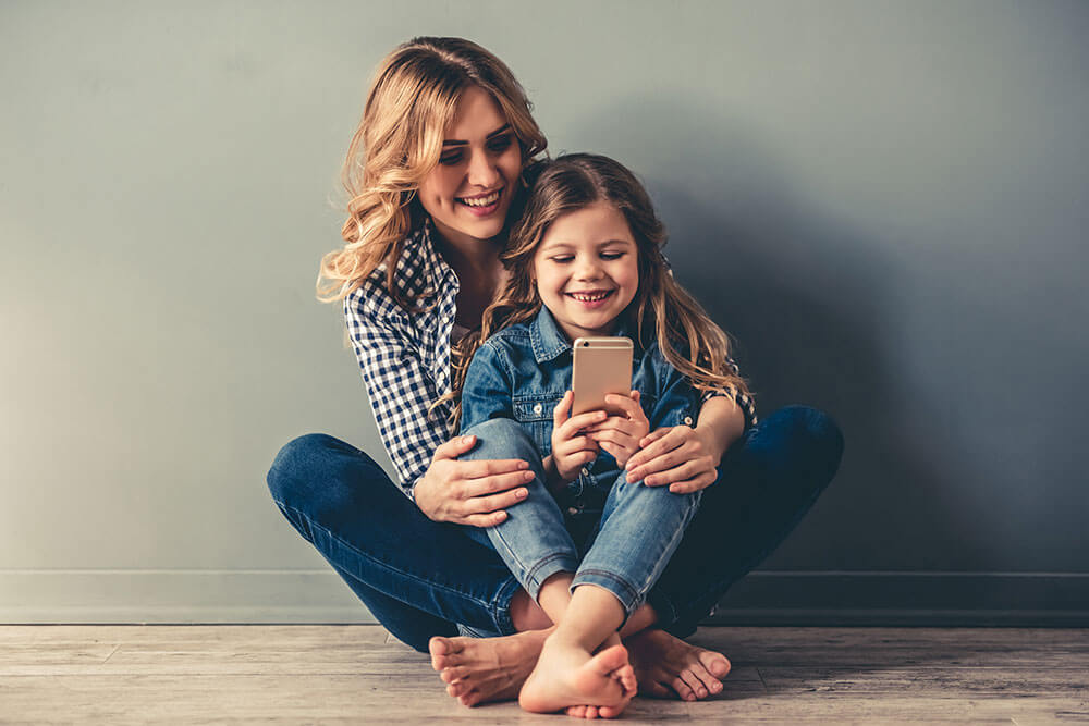 Mother and young daughter smiling while looking at an iphone