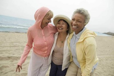 Three friends smile and walk on the beach. Their teeth are white and straight from restorative dentistry procedures.