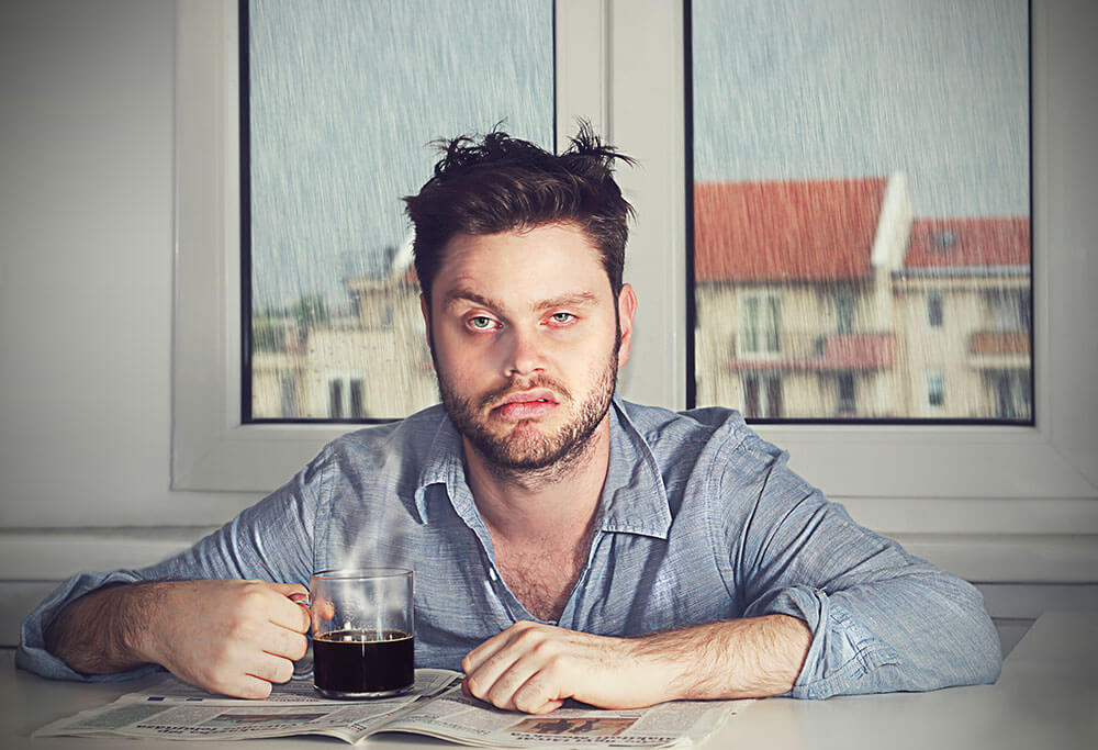 a tired looking young man with coffee