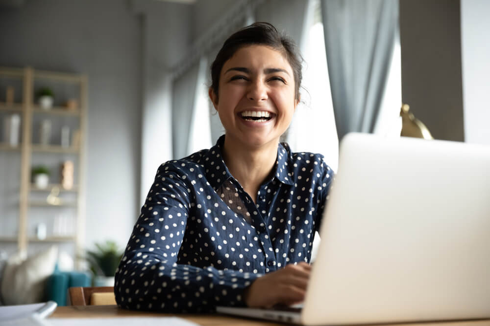 Young woman laughing at her desk