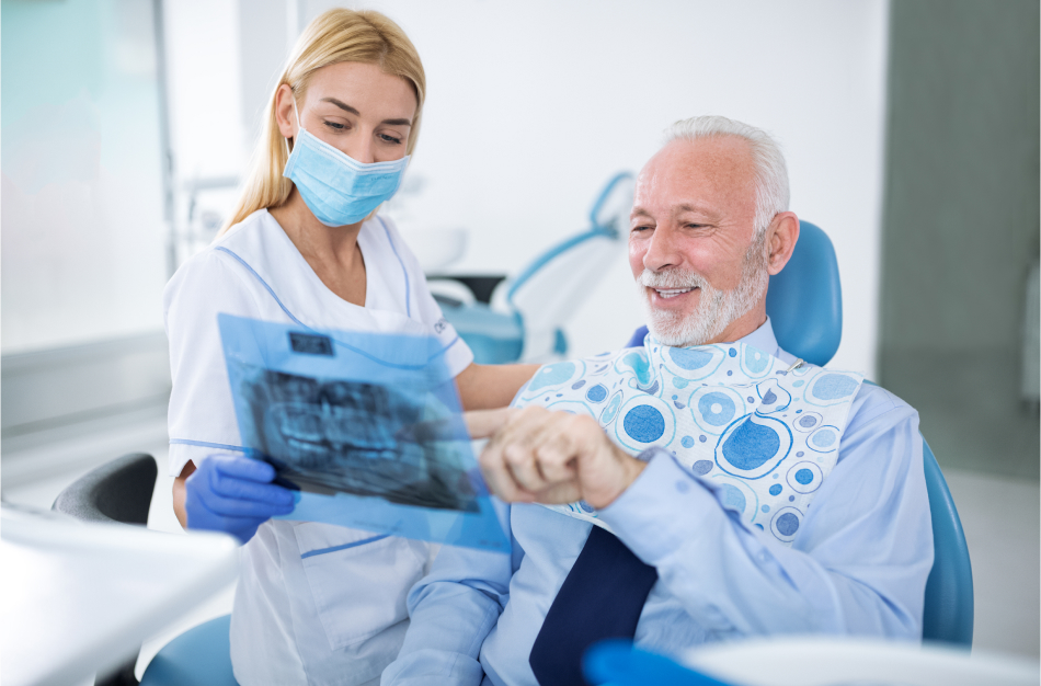 A woman wearing scrubs, blue gloves, and blue face mask shows a dental x-ray to an older man sitting in the treatment chair