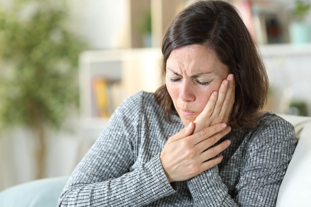 A woman clutches her jaw and twists her face in pain. She needs TMJ relief.