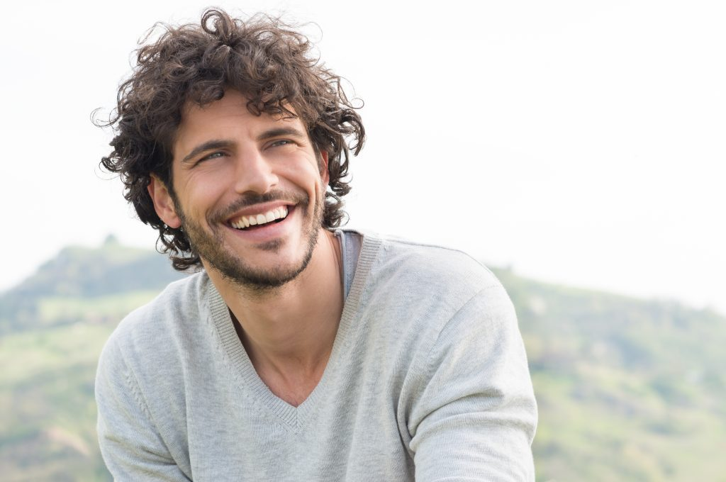A young man on a mountain smiles and gazes into the distance, showing off his smile makeover.